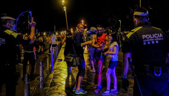 Agentes de policía desalojan a grupos de turistas y lugareños reunidos en la playa de la Barceloneta en Barcelona, España, el 10 de julio de 2021. (REUTERS/Nacho Doce).