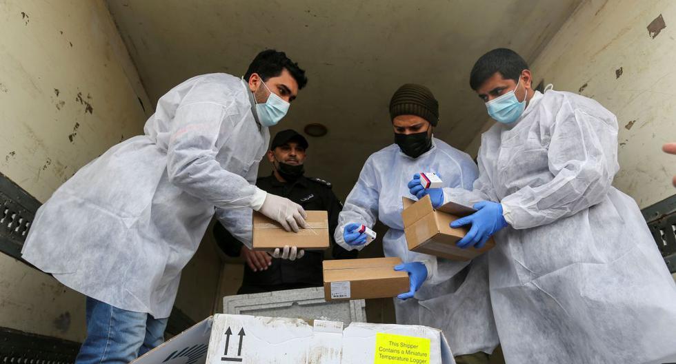 Trabajadores palestinos descargan el primer cargamento de vacunas contra el coronavirus (COVID-19) en el sur de la Franja de Gaza, el 17 de febrero de 2021. (REUTERS/Ibraheem Abu Mustafa).
