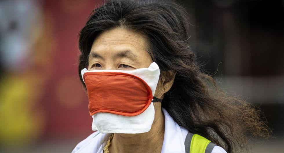 Fotografía de una mujer usando una máscara improvisada mientras camina por las calles de Guangzhou. (EFE).