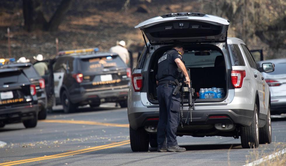 Un oficial de policía agarra un rifle de un vehículo patrulla durante un enfrentamiento con una persona en la zona de incendio evacuada cerca de Lake Berryessa, California. (Foto: EFE / Peter Dasilva).