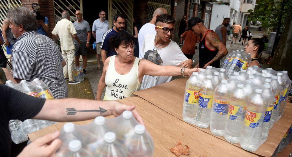La empresa que abastece energía envío botellas de agua para los usuarios afectados del Barrio de Villa de Parque, uno de los más afectados por los cortes de energía, este viernes, en Buenos Aires (Argentina). (EFE).