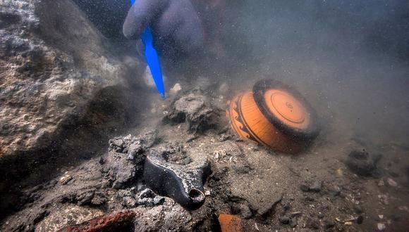 Una imagen distribuida por el Ministerio de Turismo y Antigüedades de Egipto el 19 de julio de 2021 muestra a un buzo desenterrando piezas de cerámica en la ciudad hundida de Thonis-Heracleion en la bahía de Abu Qir, en la costa mediterránea del norte de Egipto. (Foto: Egyptian Ministry of Antiquities / AFP)