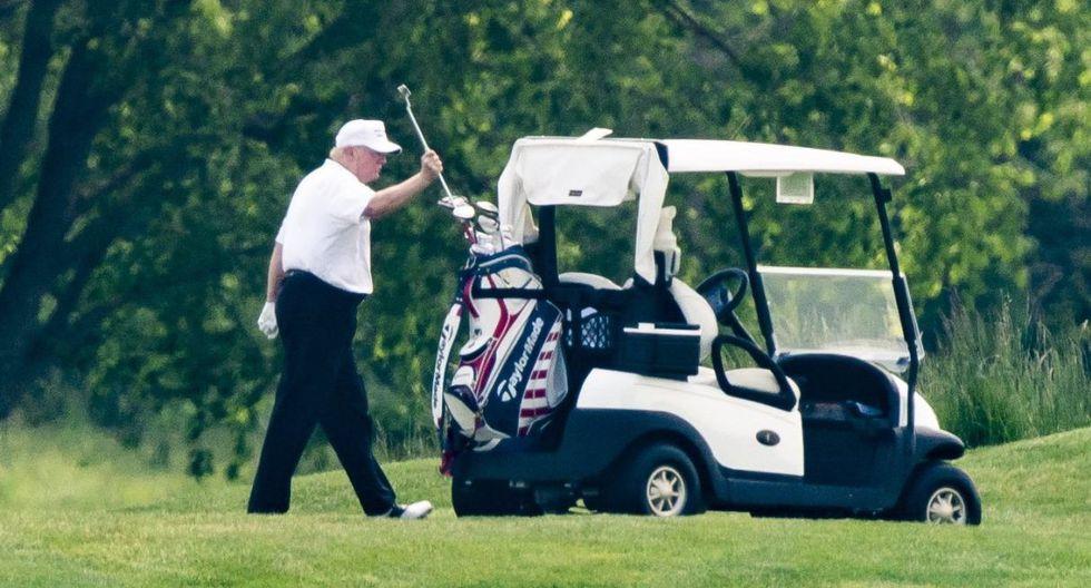 El presidente de los Estados Unidos, Donald Trump, con un sombrero y una camisa polo blanca, juega al golf en el Trump National Golf Club en Sterling, Virginia. (EFE/EPA/JIM LO SCALZO).