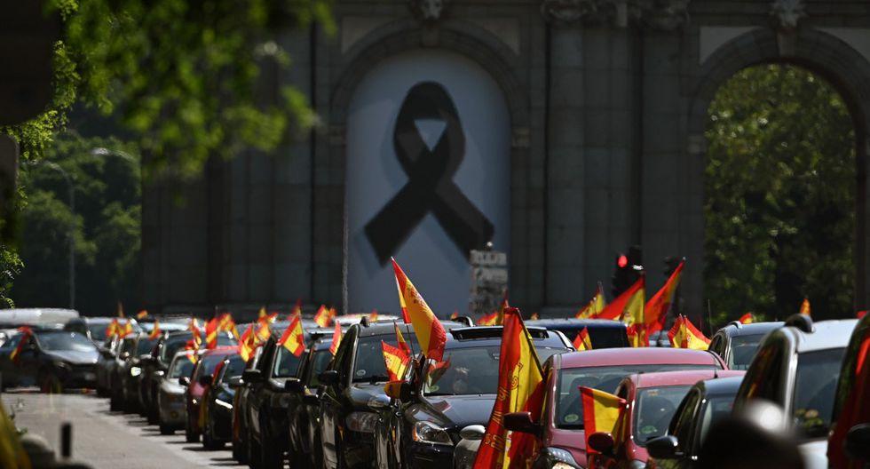 La mayoría de los autos llevaban banderas de España y pequeños grupos de personas siguieron la comitiva a pie, algunos de ellos sin respetar las normas de distancia social. (EFE/Ballesteros).