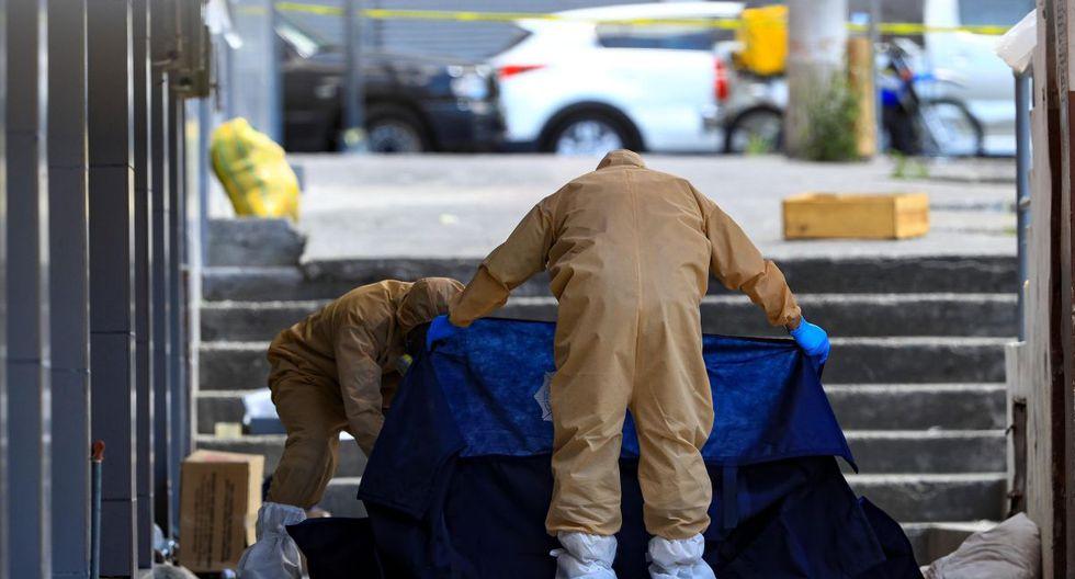 Policías con trajes especiales, como medida de protección contra la COVID-19, cubren el cuerpo de una persona que aparentemente murió por síntomas relacionados con el coronavirus. (EFE/ José Jácome).