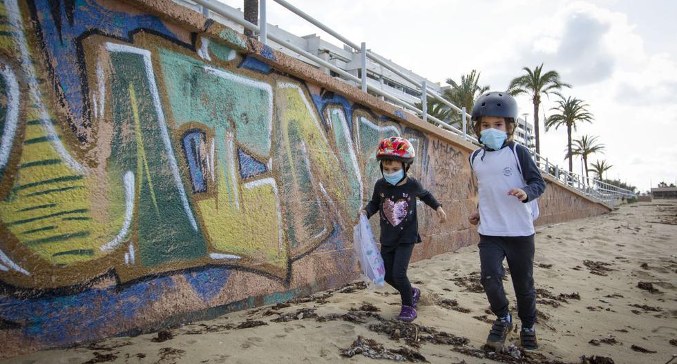 Imagen referencial. Dos niños con máscaras faciales juegan en la playa de Portixol en Palma de Mallorca, el 26 de abril de 2020. (JAIME REINA / AFP).