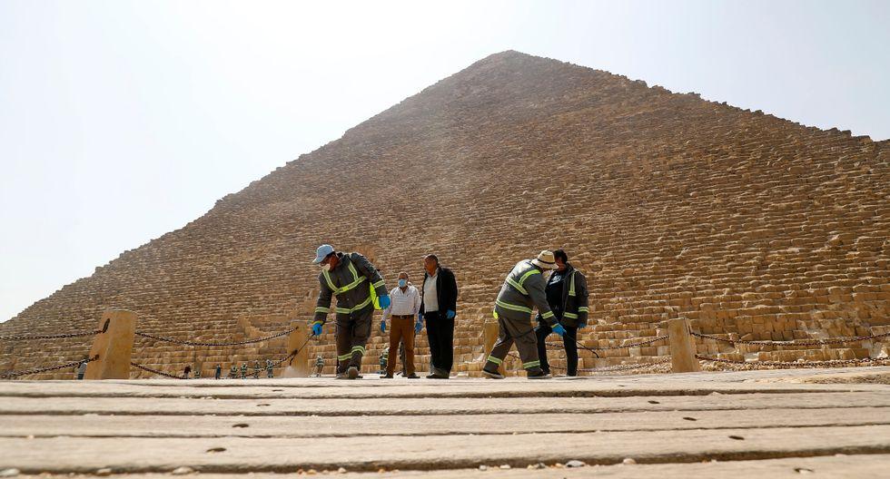 Un grupo de seis limpiadores con mascarillas y equipos de protección y fumigación se empeñaron hoy en la tarea de higienizar el entorno de las pirámides de Keops, Kefren y Micerino. (AFP).