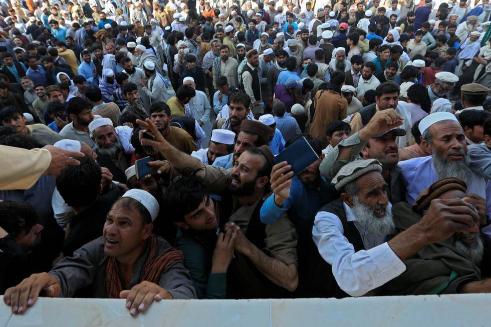 Hombres afganos esperan para recoger las fichas necesarias para solicitar la visa de Pakistán, en Jalalabad, Afganistán, el 21 de octubre de 2020. (REUTERS/Parwiz).