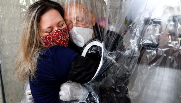 """María Paula Moraes abraza hoy su padre Wanderley de 82 años, que vive en una residencia de ancianos en la ciudad de Sao Paulo (Brasil), a través de una """"cortina de abrazos"""". (EFE/Sebastião Moreira)"""