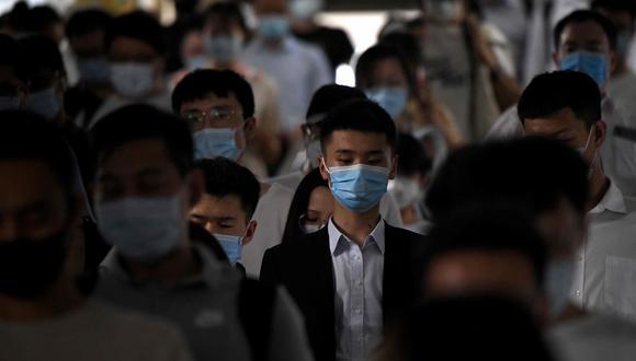 Decenas de pasajeros con máscaras faciales caminan por una estación de tren durante la hora pico en Beijing. (AFP)