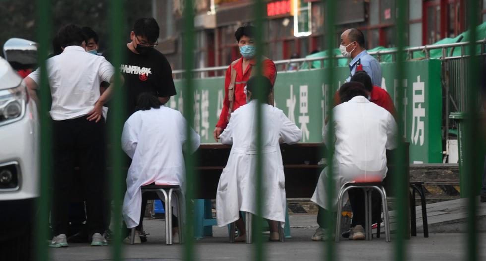 Los funcionarios se reunieron fuera del mercado mayorista de carne Xinfadi en Beijing el 12 de junio de 2020. Dos establecimientos de la capital de China fueron cerrados tras ser visitados por dos pacientes identificados con coronavirus. (GREG BAKER / AFP).