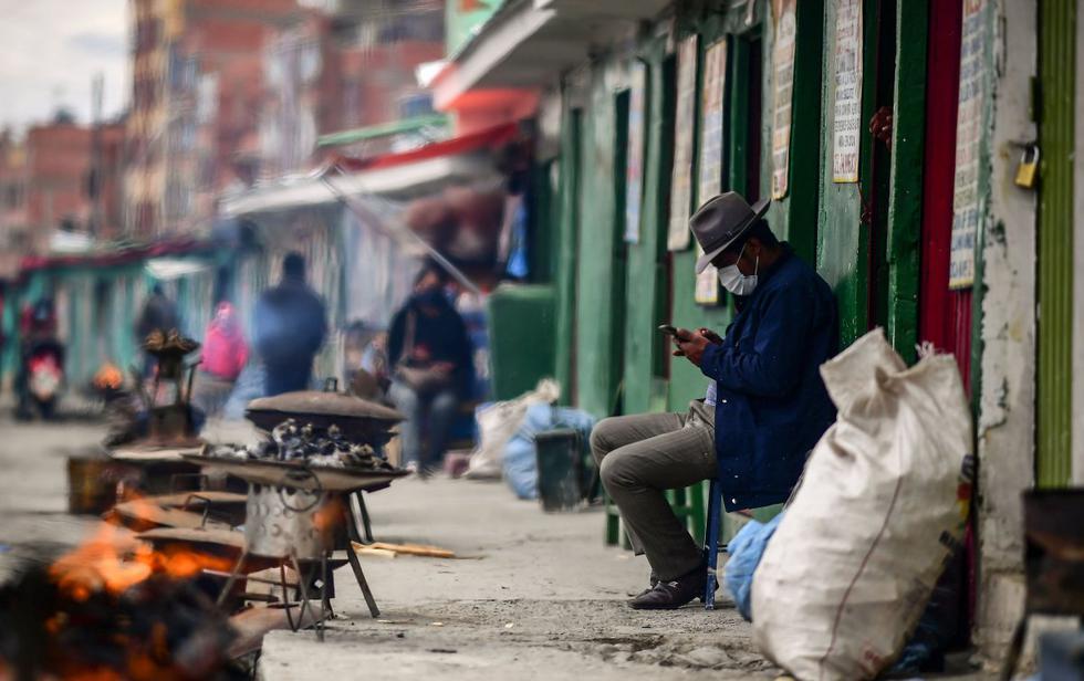 Un indígena usa su teléfono celular afuera de una sala de lectura de hoja de coca, en El Alto, Bolivia. Los chamanes aymaras se lanzan para predecir el resultado de las elecciones del 18 de octubre en el país. (AFP / RONALDO SCHEMIDT).