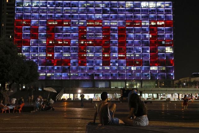 """Las ventanas del edificio del municipio de Tel Aviv-Yafo se iluminaron con la palabra """"Paz"""", en inglés, el pasado 15 de septiembre de 2020 para celebrar la firma de los históricos acuerdos de normalización israelí con los Emiratos Árabes Unidos y Bahréin. (JACK GUEZ / AFP)"""