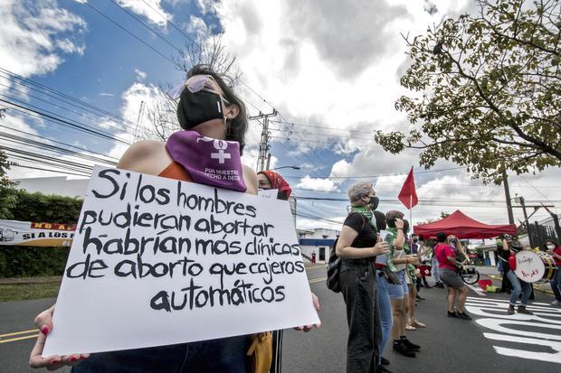 """Una mujer sostiene un cartel que dice """"Si los hombres pudieran abortar habría más clínicas de aborto que cajeros automáticos"""", durante una manifestación frente a la casa presidencial a favor de la legalización del aborto, en San José, Costa Rica, el 28 de septiembre de 2020. (Foto: Ezequiel BECERRA / AFP)"""