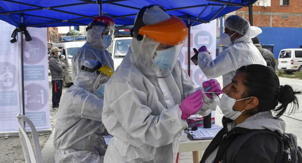 Un trabajador de salud toma una muestra de hisopo de una mujer para realizar una prueba de COVID-19 en Tranca de Urujara, La Paz, el 13 de febrero de 2021. (AFP / AIZAR RALDES).