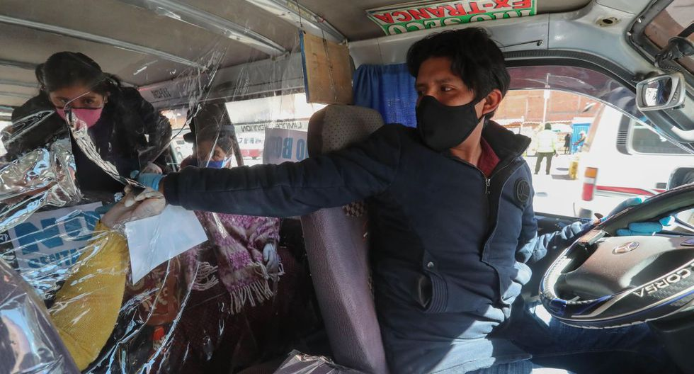 Un conductor de minibus recibe el pago del pasaje de los usuarios, este lunes en El Alto (Bolivia). La ciudad de El Alto, la segunda mayor del país con cerca de un millón de habitantes, comenzó este lunes a recuperar el transporte público como los populares minibuses, pero con medidas preventivas como la ocupación de solo una parte de su capacidad para mantener la distancia social. Bolivia encara la última semana en que está prevista la cuarentena en el país mientras sigue el aumento de casos de coronavirus, con 250 fallecidos y 6.263 positivos entre sus cerca de once millones de habitantes. (EFE/ Martin Alipaz).