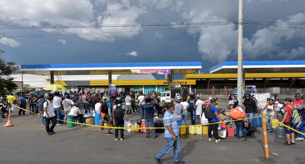 La gente hace fila para comprar gasolina afuera de una estación de servicio durante una escasez de combustible en Cali, Colombia, el 6 de mayo de 2021. (Luis Carlos AYALA / AFP).