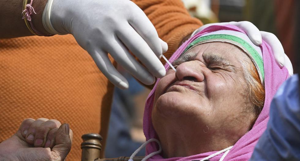 Un trabajador de la salud toma una muestra de un hisopo nasal de una mujer para realizar la prueba del coronavirus en Srinagar (India), el 21 de abril de 2021. (TAUSEEF MUSTAFA / AFP).