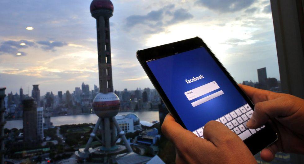 Imagen referencial. Un hombre sostiene un iPad con una aplicación de Facebook en un edificio del distrito financiero de Pudong en Shanghái. (REUTERS/Carlos Barria).