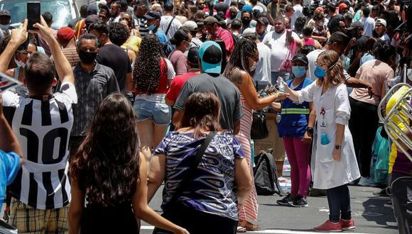 Una enfermera desinfecta las manos de las personas que caminan en una concurrida vía comercial hoy, en el centro de Sao Paulo. EFE/ Sebastiao Moreira