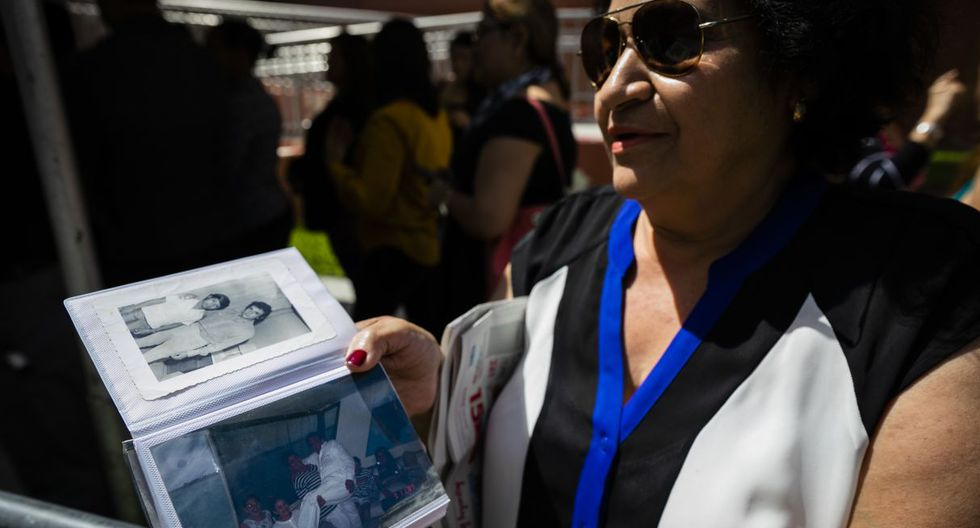 Lucila Diaz, who worked for five years with the singer Jose Jose, shows a picture of her with the singer, while she waits in line outside of the Miami-Dade County Auditorium  during a public funeral for the late singer in Miami, Florida on October 6, 2019. - The artist born Jose Romulo Sosa Ortiz, who died last Saturday at age 71, is being honored at a funeral home southeast of Miami. (Photo by Eva Marie UZCATEGUI / AFP)