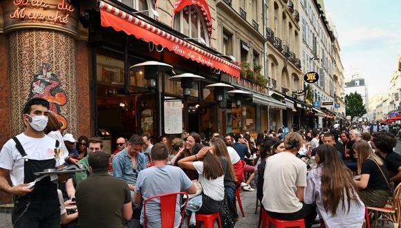 """Un camarero que usa una mascarilla facial sirve a los clientes en la terraza del café restaurante """"Le Bar du Marche"""", en París, el pasado 2 de junio, mientras los cafés y restaurantes reabren en Francia con la relajación de las medidas de confinamiento tomadas para frenar la propagación de COVID-19. (BERTRAND GUAY / AFP)"""