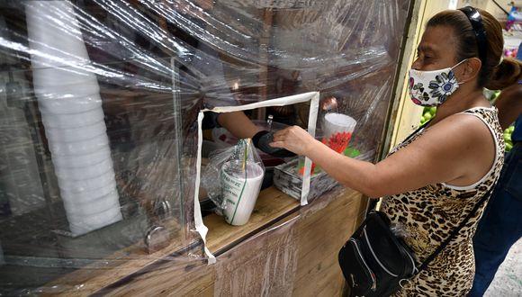 Una mujer compra en una tienda a través de una protección plástica para evitar la propagación del nuevo coronavirus, COVID-19, en el Mercado Martínez de la Torre en la Ciudad de México. (Foto: AFP/ALFREDO ESTRELLA)