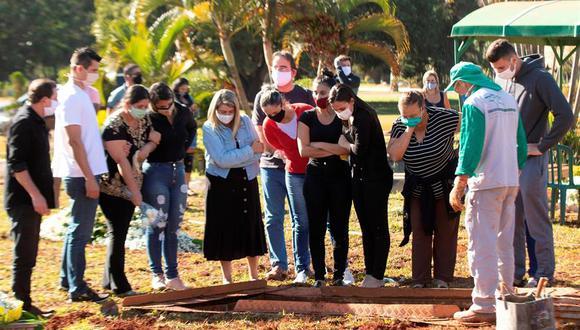 Familiares de una víctima mortal de coronavirus asisten al entierro este miércoles, en el cementerio de Campo da Esperança, en Brasilia. (EFE/Joédson Alves).