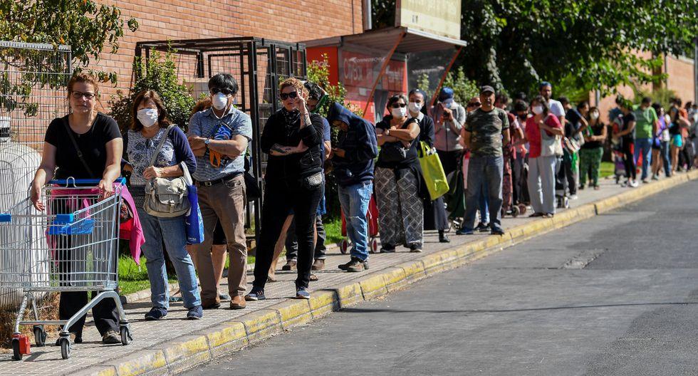 Las filas se repetían en verdulerías y pequeñas tiendas de los barrios, pero también en oficinas del Registro Civil o en notarías. (AFP).