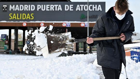 Un hombre limpia la nieve fuera de la estación de tren de Atocha en Madrid. (Foto de GABRIEL BOUYS / AFP).
