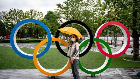 Una mujer posa con los Anillos Olímpicos frente al Museo Olímpico de Japón en Tokio (Japón), el 8 de julio de 2021. (Philip FONG / AFP).