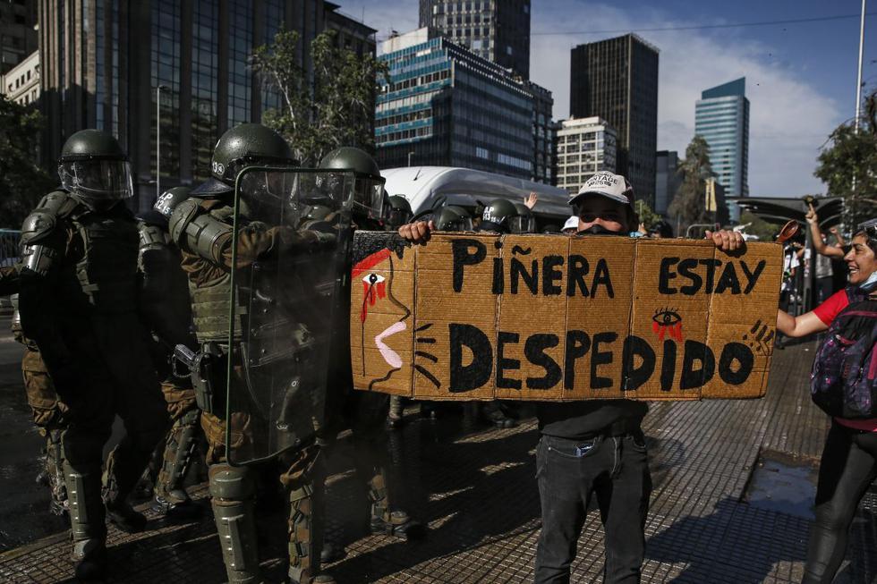 """Un manifestante sostiene un cartel que dice """"Pinera estay despedido"""" junto a la policía antidisturbios. (Foto de JAVIER TORRES / AFP)."""