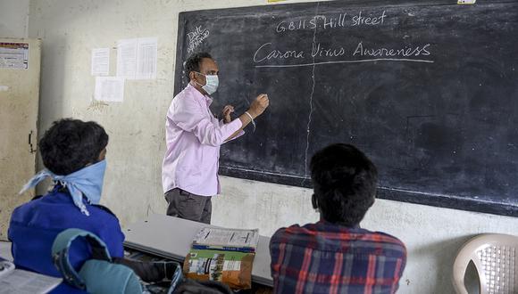Un maestro con una máscara facial enseña mientras los estudiantes asisten a clases en una escuela secundaria administrada por el gobierno en Secunderabad, la ciudad gemela de Hyderabad, en la India. (Foto: AFP)
