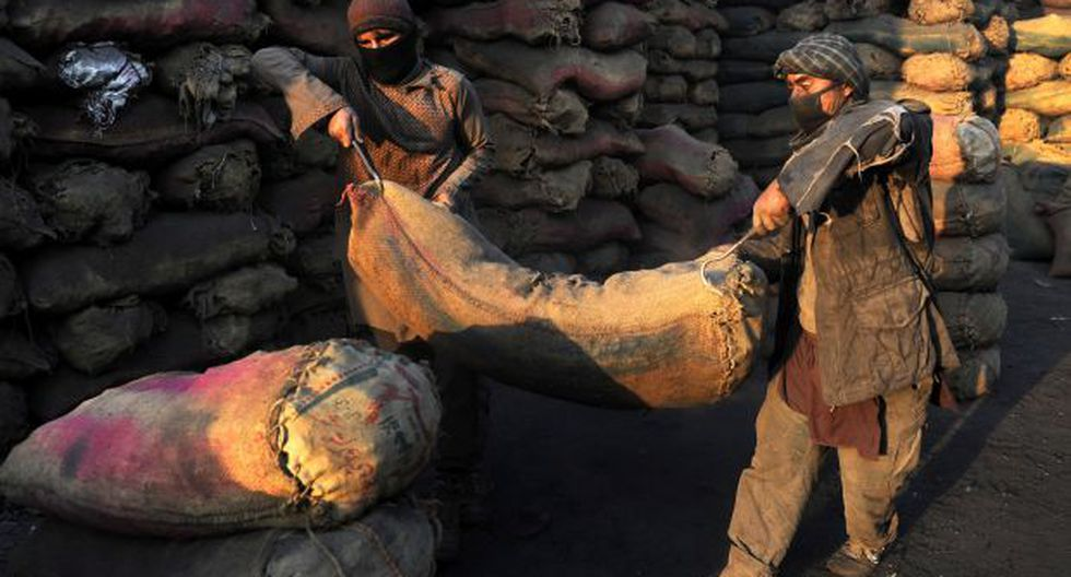 Trabajadores afganos llevan un saco de carbón triturado en un mercado de venta de carbón en las afueras de Kabul, Afganistán. (Foto referencial: EFE)