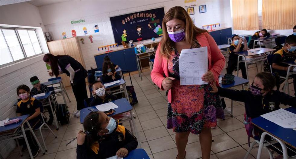 Una docente es vista con un grupo de alumnos durante una clase en el Colegio Polivalente Patricio Mekis durante la primera jornada de inicio del curso escolar 2021, en Santiago (Chile). EFE/Alberto Valdés