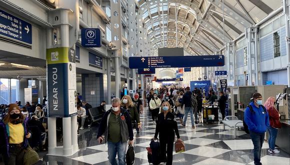 Viajeros utilizan mascarillas mientras caminan por el aeropuerto internacional de Chicago O'Hare, donde un hombre estuvo escondido desde octubre por miedo al COVID-19. (Daniel SLIM / AFP)