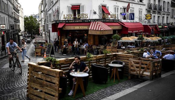 Esta foto de archivo tomada el 23 de julio de 2020 muestra a personas tomando bebidas en la terraza extendida de un café hecho con paletas de madera en París, en respeto al distanciamiento social debido a la pandemia del coronavirus. (AFP/Christophe ARCHAMBAULT).