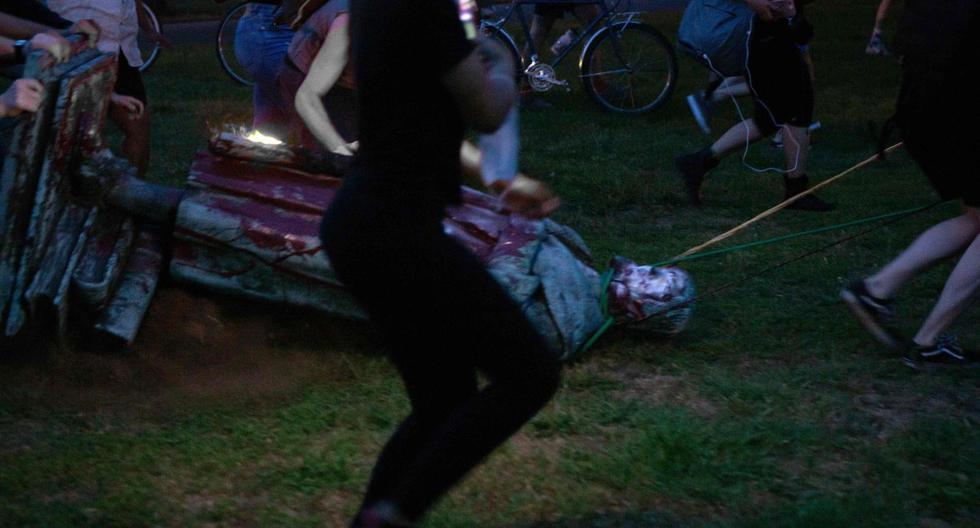 Los manifestantes arrastran una estatua de Cristóbal Colón a un estanque cercano después de derribarla en Richmond, Virginia, el 9 de junio de 2020. (AFP / Parker MICHELS-BOYCE).