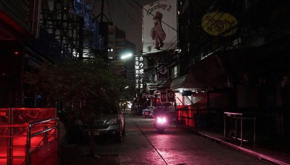 Esta foto tomada el 4 de abril de 2020 muestra una motocicleta que pasa por la calle cerrada de Soi Cowboy, en Bangkok, una carretera generalmente ocupada con trabajadoras sexuales y clientes, pero ahora cerrada por las autoridades buscando detener la propagación del coronavirus. (Foto: AFP/Aidan Jones)