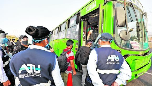 Fiscalizadores de la ATU supervisan el acceso de pasajeros a los buses de transporte urbano.