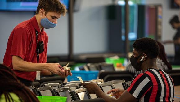 Un trabajador que usa una máscara cuenta el cambio para un concursante en North Austin Bingo en Austin, Texas. (Foto: Sergio Flores / AFP)