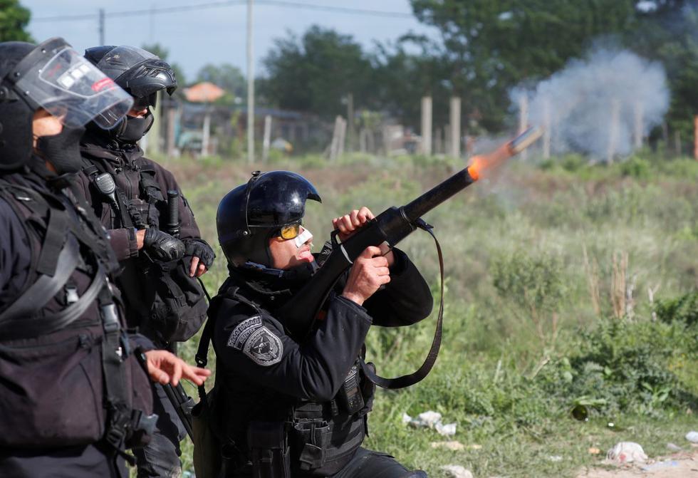 Un policía que lleva a cabo un desalojo dispara un cañón de gas lacrimógeno mientras chocan con los ocupantes ilegales en Guernica, provincia de Buenos Aires, Argentina. (REUTERS/Agustin Marcarian).
