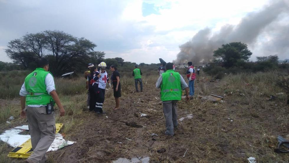 Pasajeros de avión caído en México salen caminando del lugar del accidente. (
