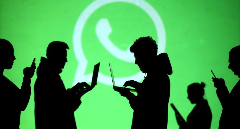 Las siluetas de los usuarios de computadoras portátiles y dispositivos móviles se ven junto a una proyección de pantalla del logotipo de Whatsapp. (REUTERS/Dado Ruvic).