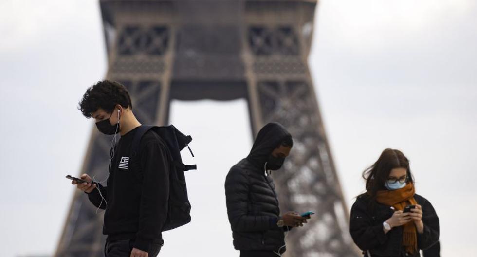 Peatones con mascarillas caminan cerca de la Torre Eiffel en París, Francia, 26 de febrero de 2021. (EFE/EPA/IAN LANGSDON).