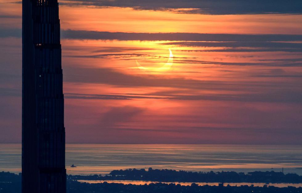 Un eclipse solar parcial se eleva entre los edificios del horizonte de Manhattan, en Nueva York. (Ed JONES / AFP)