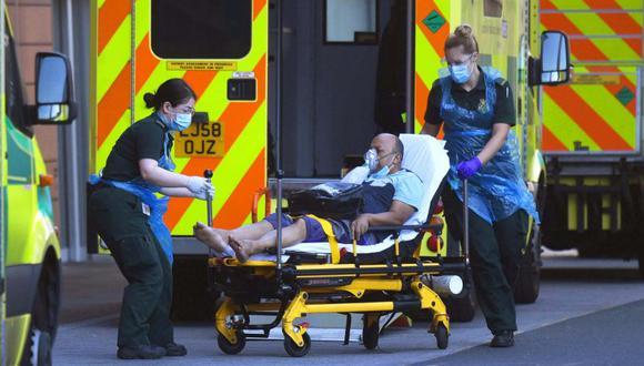 Un equipo de ambulancia usa PPE (Equipo de Protección Personal) mientras atiende a un paciente en el Royal London Hospital en Londres, Gran Bretaña. (EFE/NEIL HALL).