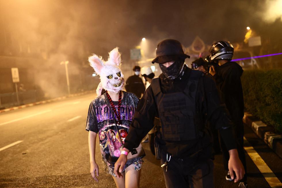 Manifestantes tailandeses, uno con una cabeza de animal y otro con equipo de protección, caminan juntos después de que la policía disparara gases lacrimógenos durante una manifestación. (Foto:  Jack TAYLOR / AFP)