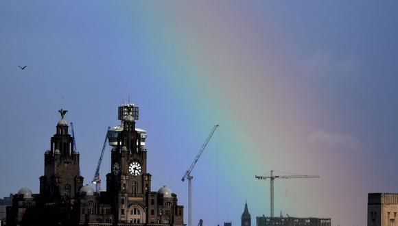En esta foto de archivo tomada el 6 de marzo de 2019, se muestra un arco iris parcial sobre el Royal Liver Building en Liverpool, noroeste de Inglaterra. (Paul ELLIS / AFP).