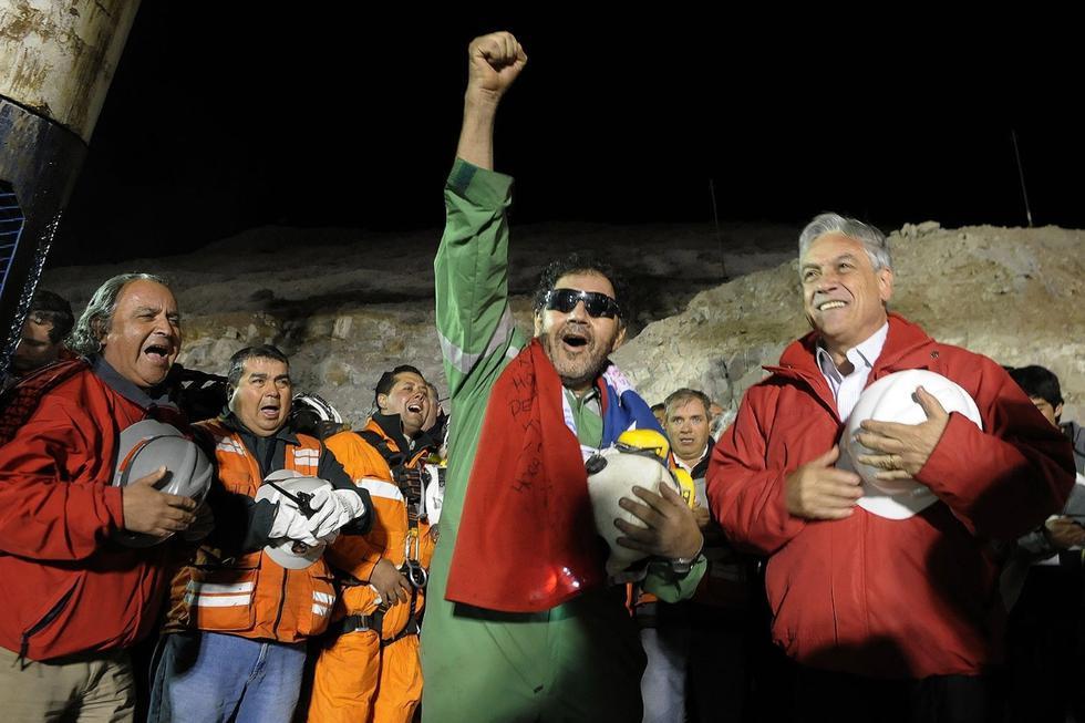 El último minero en ser rescatado, Luis Urzúa, a quien se le atribuye haber organizado a sus compañeros para racionar alimentos y salvarse, gesticula junto al presidente Sebastián Piñera en Copiapó (Chile), el 13 de octubre de 2010. (REUTERS/Alex Ibanez-Chilean Presidency).